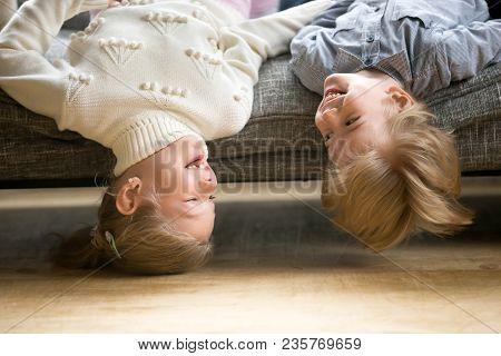 Happy Preschool Boy And Girl Lying Upside Down On Sofa, Cheerful Smiling Children Brother Sister Hav