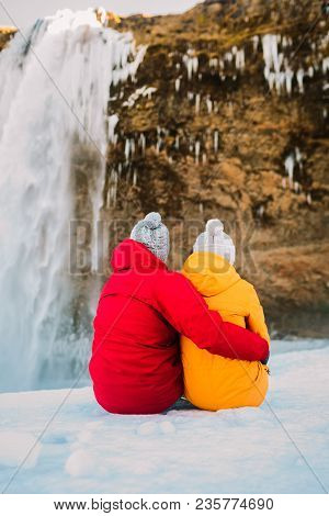 Man In Red Jacket And Woman In Yellow Jacket Sit Together Next To Waterfall. Iceland Travelers. Rear