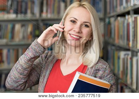Woman Student Talking On The Phone In Library