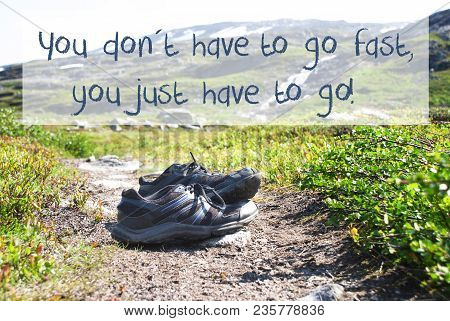 English Quote You Do Not Have To Go Fast You Just Have To Go. Trekking Shoes On Hiking Path In Norwa