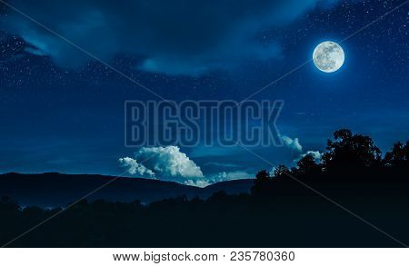 Landscape Of Blue Night Sky With Many Stars And Cloudy Above Silhouette Of Mountain Range And Trees.