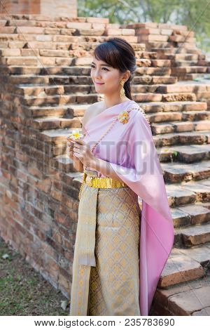Women Stand Wearing Traditional Cloth Thailand Or Thai Dress In Ancient City And Walls Background.