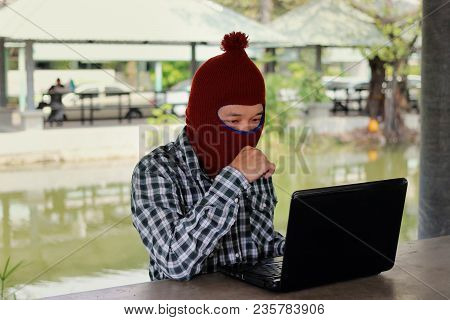 Masked Hacker In A Balaclava Sitting At A Desk Stealing Information With Laptop. Computer Criminal C