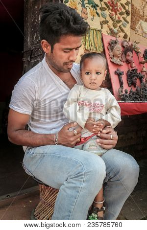Kathmandu, Nepal - September 22, 2016: Unidentified Man With His Baby Girl On His Lap In Front Of Th