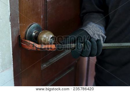Hands Of Masked Thief With Balaclava Using Crowbar To Breaking Into A House At Night Time. Crime Con