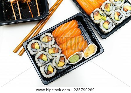 Delicious Sushi Delivery Box With Sushi California, Maki, Sashimi, Yakitori And Wooden Sticks With W