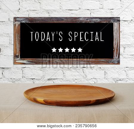 Today's Special On Vintage Chalk Board And Empty Wooden Plate On Table Background