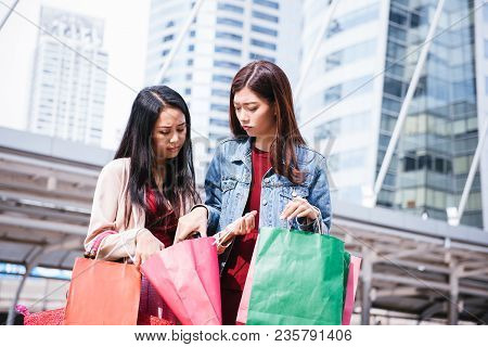 young women show shopping bag, sale, consumerism and people concept. fashion tone.