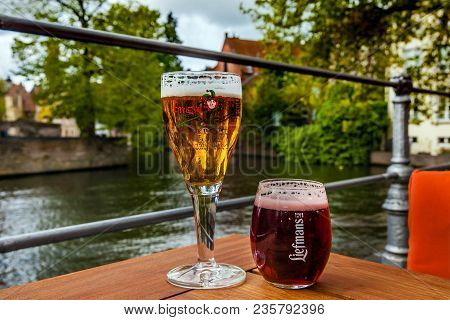 Bruges, Belgium - April, 2017: Two Glasses Of Belgian Beer Standing On The Table With The City View