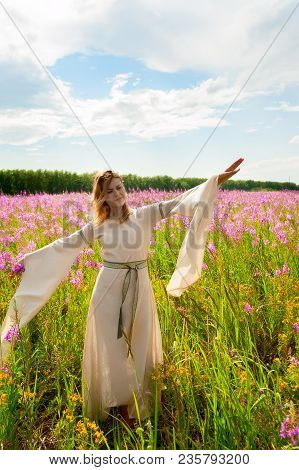 Beautiful Woman In Traditional Dress Relaxes On Fireweed Meadow