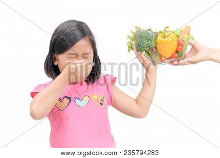 Asian Child Girl With Expression Of Disgust Against Vegetables Isolated On White Background, Refusin