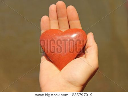 The Hand Holds A Red Or Terracotta Heart Made Of Natural Stone. Heart In Hand. A Stone In The Shape