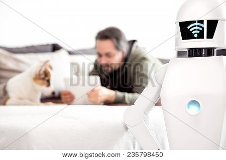 Man Is Laying On A Couch With His Puppy Dog And Uses His Tablet While His Service Household Robot Is