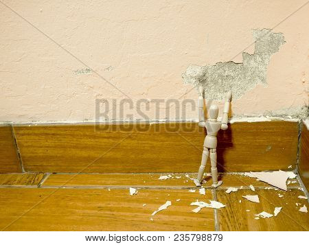 Wooden Puppet Tried To Fix Old Paint Peeling Plaster Walls Damage Surface. A Background Of Peeling P