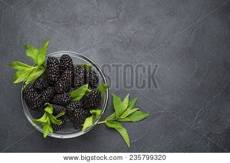 Glass Plate With Ripe Blackberries And Green Mint Leaves On A Black Surface. Macro Photo Of Ripe Bla