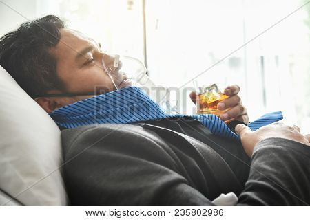 Alcohol Addicted Businessman With Oxygen Mask Is Holding Whiskey Glass While Lying On Hospital Bed.