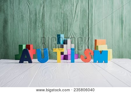 Word Autism With A Pieces Of Puzzle On White Wooden Background. Autism Spectrum Disorder (asd) Conce