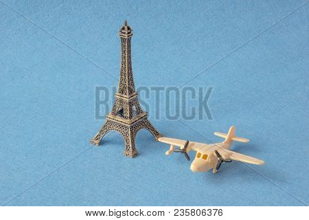 Vintage Plane Toy Traveling The World To Paris. Eifel Tower Model With Little Toy Plane On Blue Back