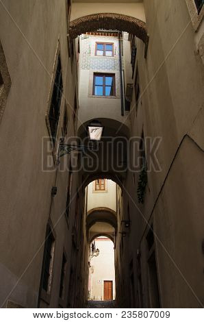 Walls And Windows Flanking, And Topping A Narrow And Tall Archway In Alfama Disctrict, The Most Famo