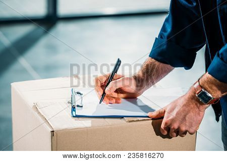 Courier Filling Cargo Declaration On Cardboard Package