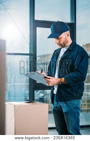 View Of Delivery Man Filling Cargo Declaration