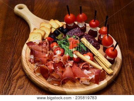 Board With Snacks On Wooden Table. Cold Appetizers With Tomatoes, Sausage, Salami, Ham, Arugula, Oli