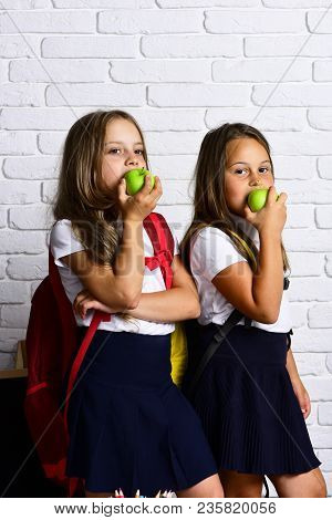 Back To School And Happy Time! Cute Children Eating Apples. Kids Are Learning In Class On Background