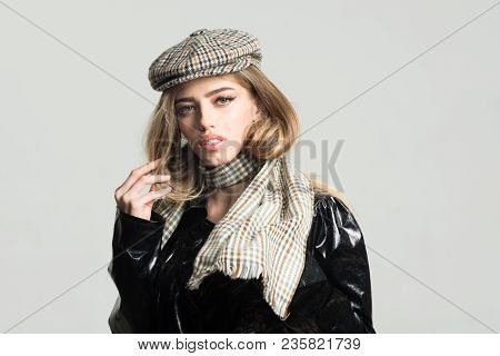 Girl with long hair wears black cloak, plaid kepi, scarf, light background, copy space. Sexy lady in spring, autumn outfit. Fashion accessories concept. Woman on calm face in cloak with accessories. poster