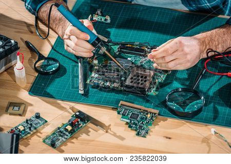 Close-up View Of Engineer Soldering Pc Parts