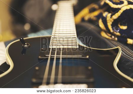 Strings, Pickup, And Toggle Switch In Focus On A Black And Blue Electric Guitar.