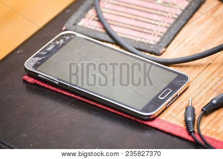 Modern Cell Or Mobile Phone With Cracked Screen Sitting On Table.