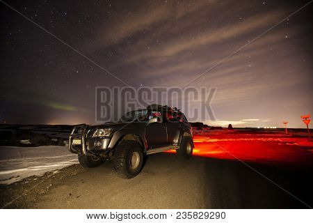 A Car Sits On The Road Surrounded By The Beautiful Night Sky In Iceland