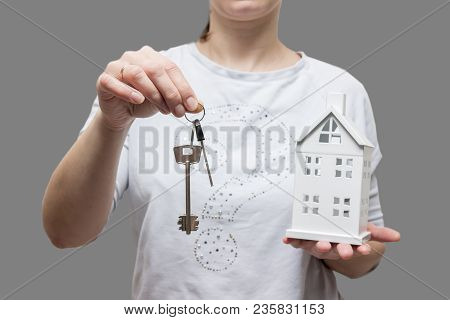 Keys From House Concept. Woman Holds Small House And Keys In Her Hand. Buy Real Estate. Real Estate