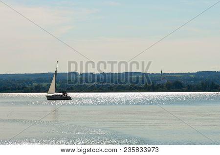 A Single Sailboat On A Calm Lake