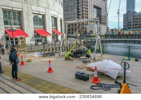 West India Quay, London, Uk - March 26, 2017: Workmen In High Viz Jackets Hoisting A Large Stone Bes