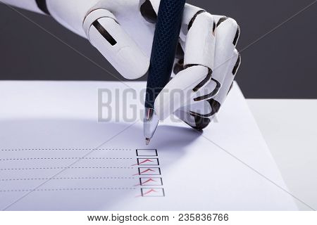 Close-up Of A Robot Hand Ticking Off Checkboxes On Document With Pen
