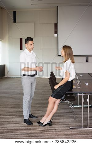 Serious Colleagues Talking In Boardroom Before Meeting With Banquet. Young Caucasian Male And Female