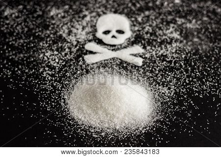 Skull And Bones Over A Hill Of Granulated Sugar On A Black Background. The Concept Of Sugar Kills.