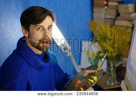Artist Holds A Palette In His Mouth. He Holds Palette With Oil Paints And Brushes. Canvas And Flower
