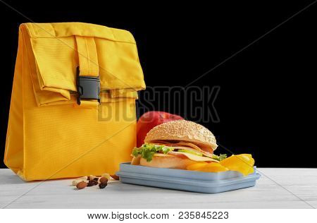 Lunch Box With Appetizing Food And Bag On Table
