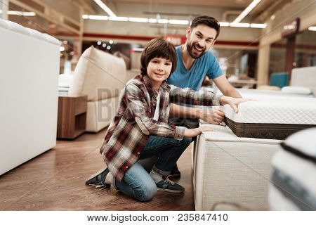 Bearded Man With Young Son Is Testing Mattress For Softness. Testing Softness Of Mattress. Choosing