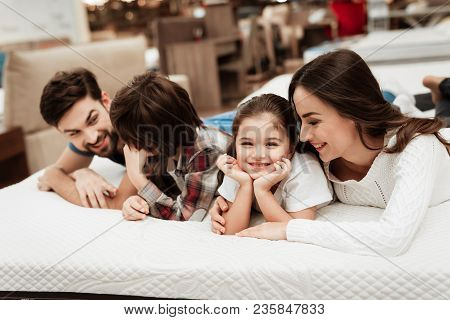 Young Happy Family Checks On Softness Of Orthopedic Mattress, Lying On Bed In Furniture Store. Young