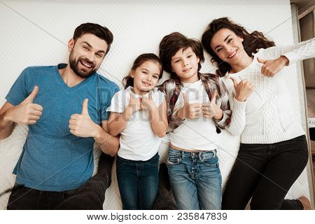 Happy Family Enjoys Comfort Of Lying On A Mattress Inside A Furniture Store. The Best Choice Of Orth