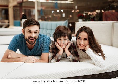 Lovely Bearded Man, Together With His Beautiful Wife And Son, Relaxes On The Mattress In The Store.
