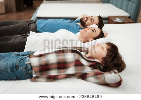 Young Happy Couple With Cute Little Boy Lies On Bed In Mattress Store. Family Checking Softness Of M