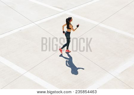 Young, Fit And Sporty Girl Running Outdoor.