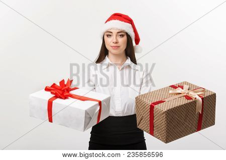 Christmas Concept - Young Happy Caucasian Business Woman With Santa Hat Giving A Choice Of Gift Boxs