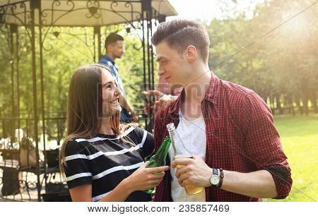 Smiling Young Couple With Beer And Looking At Each Other While Two People Barbecuing In The Backgrou