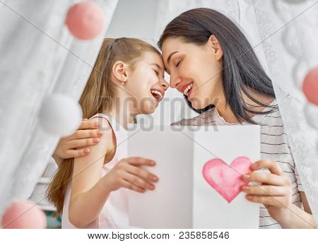 Happy women's day! Child daughter is congratulating mom and giving her postcard. Mum and girl smiling and hugging. Family holiday and togetherness.