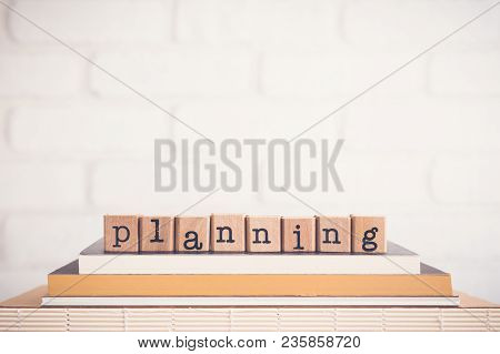 The Word Planning, Alphabet On Wooden Cubes On The Books. Background Copy Space, Vintage Minimal.  T